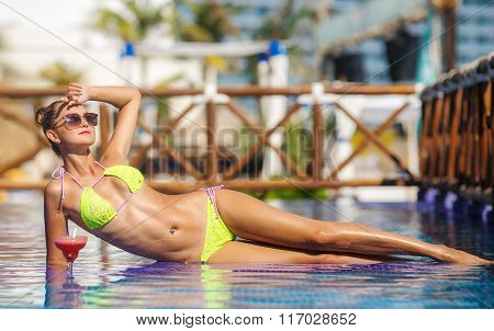 Beautiful girl with a cocktail in a blue pool
