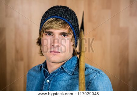 Close up of hipster standing with axe against wooden wall