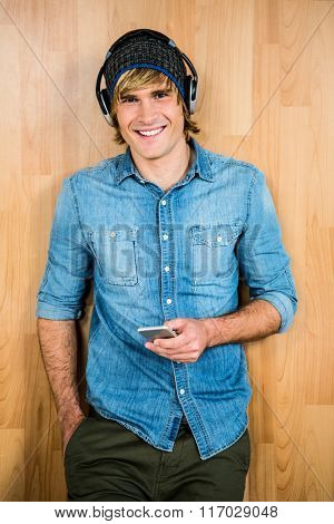 Smiling hipster listening to music with wooden background