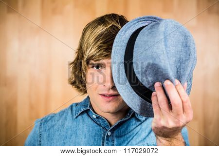 Focused hipster man hiding his face with hat