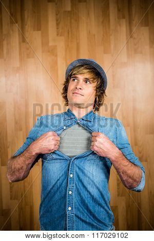 Funny blond hipster taking off his shirt with wooden background