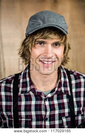 Smiling blond hipster staring at camera with wooden background