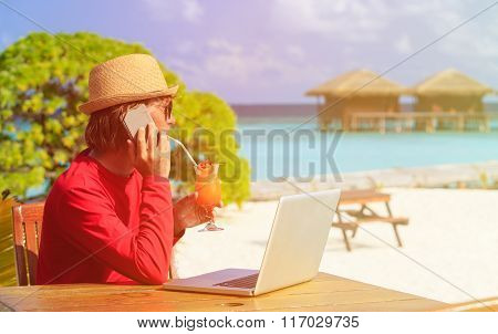 Young man with laptop and cocktail at beach