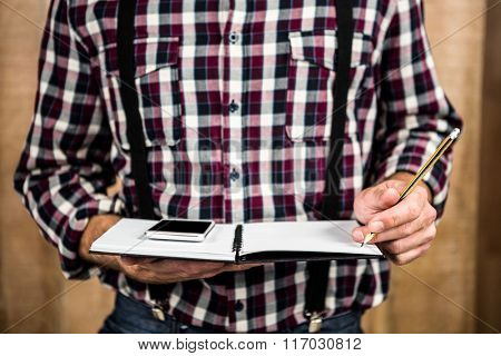 Hipster man writing on notebook with wooden background
