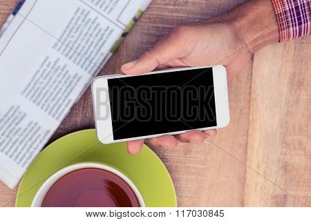 Cropped image of man using smart phone by coffee and newspaper on table