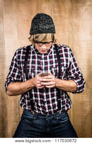 Focused blond hipster holding smartphone with wooden background