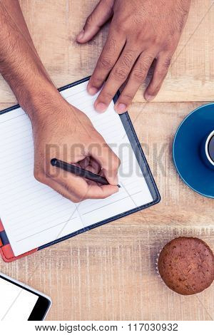 Cropped image of person writing on diary at table