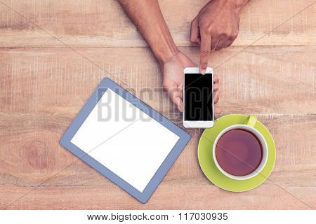 Cropped image of man using smart phone by coffee and tablet on table