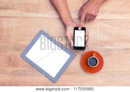 Overhead view of person using smart phone by coffee and tablet on table