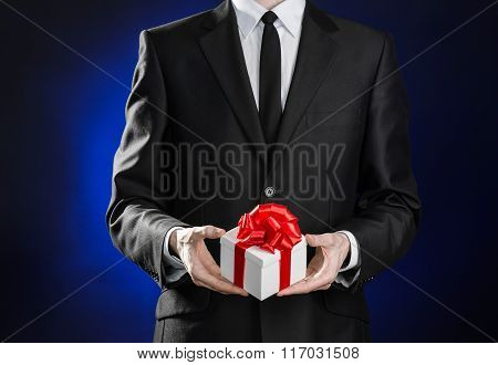 Theme Holidays And Gifts: A Man In A Black Suit Holds An Exclusive Gift In A White Box Wrapped With