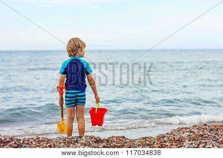 little blond kid boy standing on lonely ocean beach