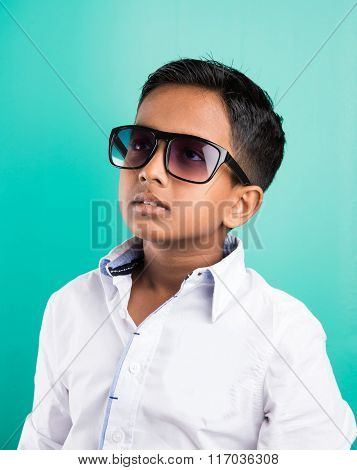 indian kid wearing dark glasses or Goggles, isolated on green, 10 year indian boy in goggles, side p