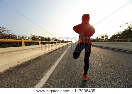 young fitness woman runner warm up on city road