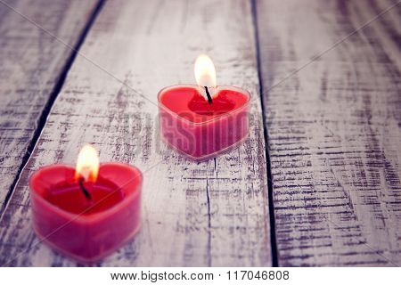 Red Burning Heart Shaped Candles On Rustic White Wooden Table. Valentine's Day And Mother's Day Back