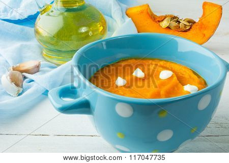 Creamy Pumpkin Soup With Cream In A Blue Bowl