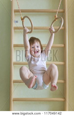 Baby Doing Exercises On Gymnastic Rings.