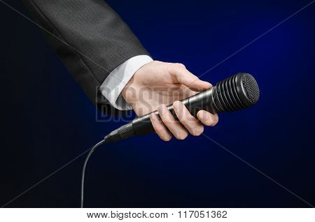 Business Speech And Topic: A Man In A Black Suit Holding A Black Microphone On A Dark Blue Backgroun
