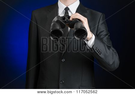 Business And Search Topic: Man In Black Suit Holding A Black Binoculars In Hand On A Dark Blue Backg