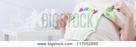 Pregnant Woman Holding Babywear