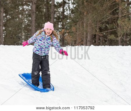Girl Standing On Sled And Snow Surfing Down Hill