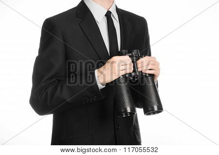 Business And Search Topic: Man In Black Suit Holding A Black Binoculars In Hand On White Isolated Ba