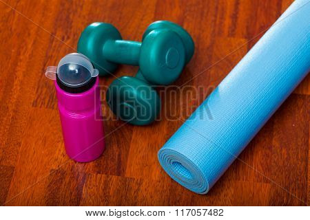 Two dumbbells with water bottle and yoga mat, sporty lifestyle concept