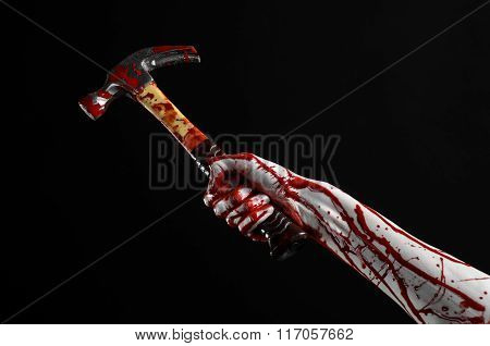 Bloody Halloween Theme: Bloody Hand Holding A Bloody Hammer Isolated On A Black Background