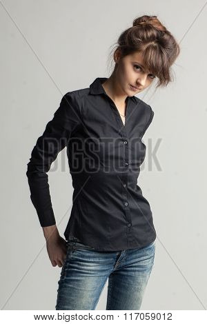 Elegant Woman In Black Shirt And Jeans Isolated On Gray Background