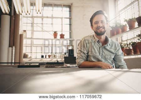 Designer entrepeneur looking relaxed in his studio with sunflare