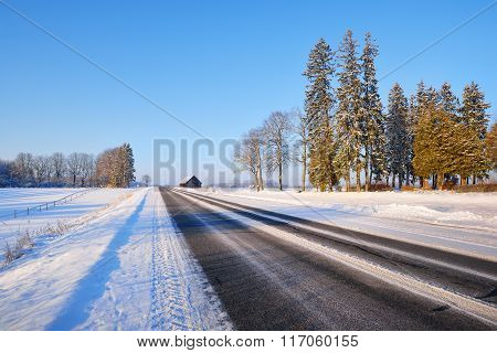 Winter Highway On A Sunny Day With Snowy Trees, Bus Stop And A Rural Cottage
