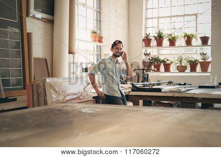 Craftsperson talking on phone in workshop studio
