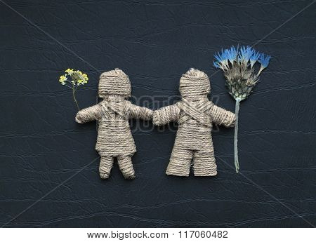 A Boy And A Girl Made Of Hemp Ropes Are Holding Flowers. Be My Valentine