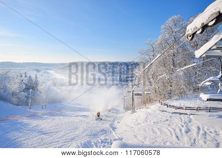 Chair Lift For Skiing Covered In Snow And Hoarfrost With A Skiing Slope View And Snow Cannons