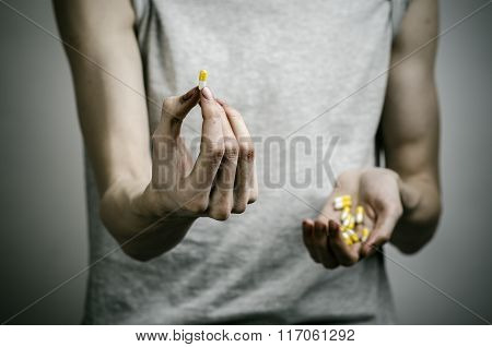 He Fight Against Drugs And Drug Addiction Topic: Addict Holding A Narcotic Pills On A Dark Backgroun