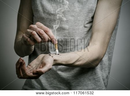 Cigarettes, Addiction And Public Health Topic: Smoker Puts His Hand On The Cigarette On A Dark Backg