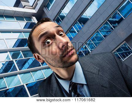 Surprised businessman against office building background