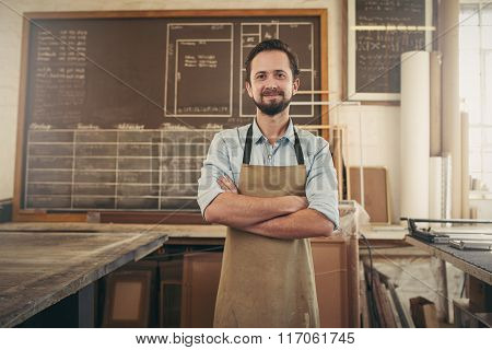 Positive craftsman in his workshop with arms folded