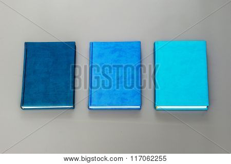 Three blue diary on a gray background