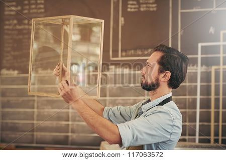 Crafstman entrepreneur inspecting a new wood and glass design