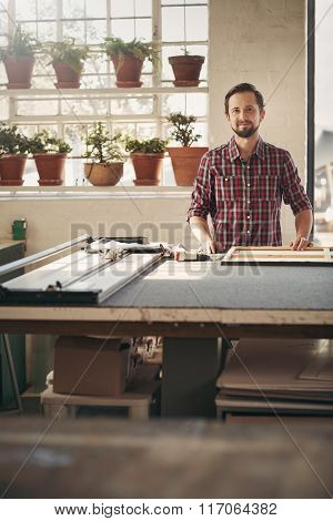 Proud entrepreneur in his worshop studio with beautiful light