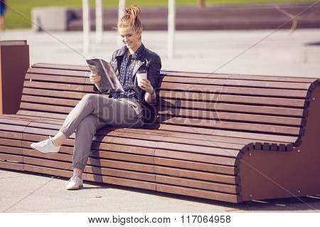 Smiling Woman Sitting On A Bench With Coffee And Reading Magazine