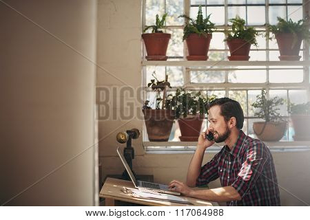 Smiling designer talking on phone at his studio desk