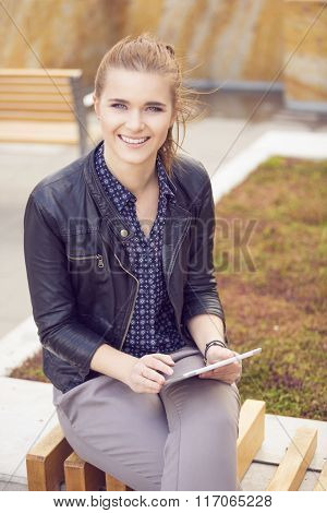 Beautiful Woman Sitting On A Bench With Tablet