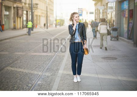 Woman Talking On The Phone On City Promenade