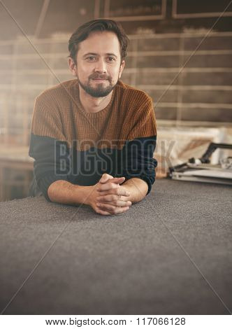 Young casual man looking thoughtful in his studio