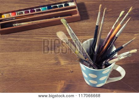 Old Paintbrushes In A Mug Or Cup With Watercolor Or Watercolour Paint