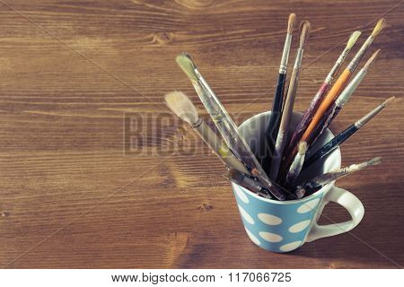 Old Paintbrushes In A Mug Or Cup