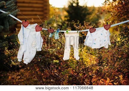 Baby's Clothes Are Hanging And Dryingon A Clothesline Outdoor In