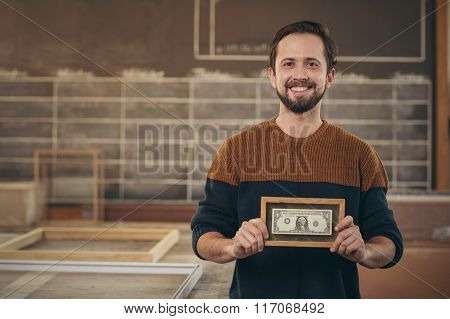 Craftsman entrepreneur proudly displaying a framed bank note