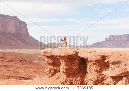 Cowboy Caught In Sun On Rock Bluff In Monument Valley Utah Usa